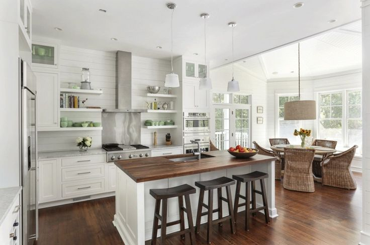 An elegant open-concept kitchen with an adjacent dining space, bay windows, and a single white island with butcher block countertops and a single basin stainless steel sink.  Shiplap Backsplash.