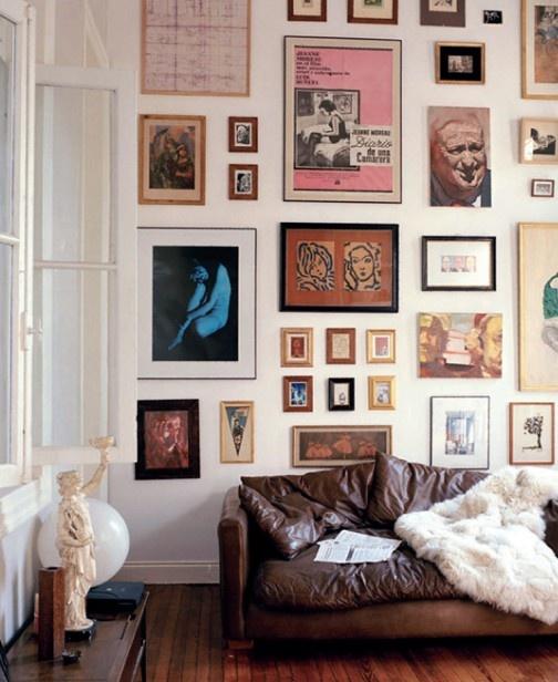 een muur vol schilderijen en een ingeleefde zetel
