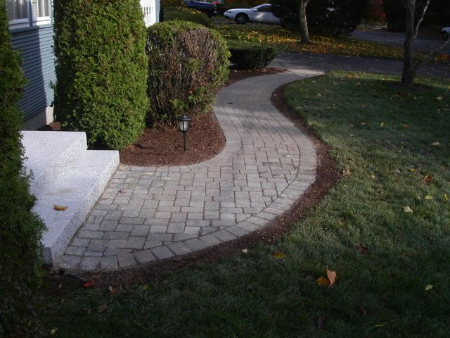 Walkway of concrete pavers curves perfectly to a large granite step and landing.