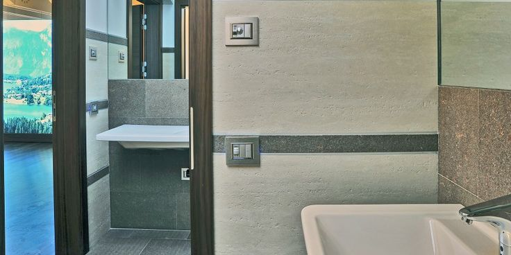 Rural Bank – Baselga di Pine' (TN) – Italy At the rural #bank in Baselga Travertino Romano Scanalato was used for the #bathroom tiling in #White. An unusual combination, that of a #porcelain #stoneware tile that faithfully reproduces the structure and grain of #natural #stone with #anthracite #granite #inserts and metal rods used as finishing complements.