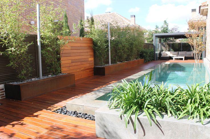 Piscina desbordande con jardinera de obra acompañada de agapantos y jardineras de acero corten con pantallas de bambúes en los laterales