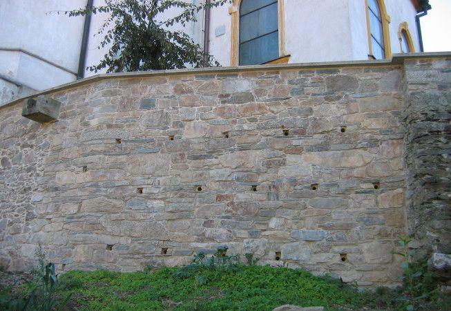 Obnova opěrné zdi – Červená Lhota uTřebíče, kostel Ruly, amfibolity a syenity (durbachity) z původní zdi a polního sběru. Pískovcové žlaby a záklopové desky z mrákotínské žuly, z lomu Mrákotín I.  Obnova zřícené opěrné hřbitovní zdi. Sklonitá, opěrná zeď s divokou vazbou s ložně ukládanými kameny do přibližně vodorovných řádků, s nepravidelnou, šíbrovanou spárou, odvodňovacími otvory a zalomením. Levá část zdi je původní, pouze nově vyspárovaná. | KA-STA – Kamenné stavby