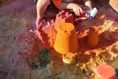 Coloured water spray bottles in the sand-pit