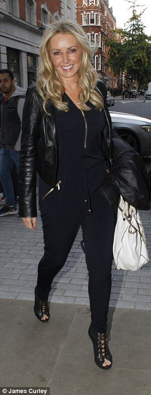 What a difference a day makes: Carol Vorderman showed she does off duty style just as well as red carpet glamour as she rocked a leather jacket and casual black jumpsuit at the BBC Studios in London on Tuesday
