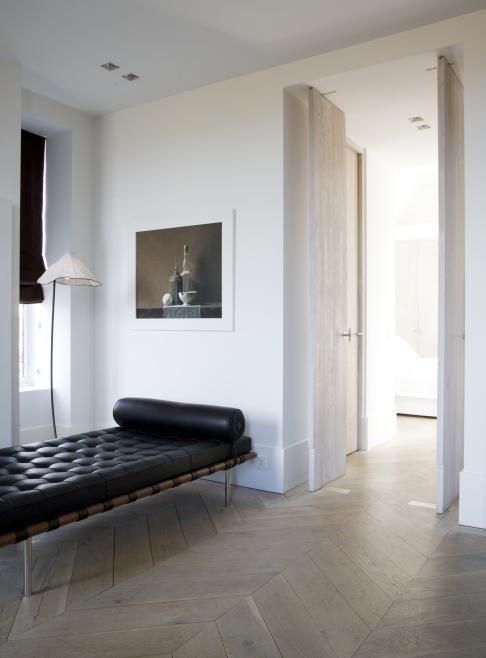 Elegant space with Barcelona daybed & herringbone floors
