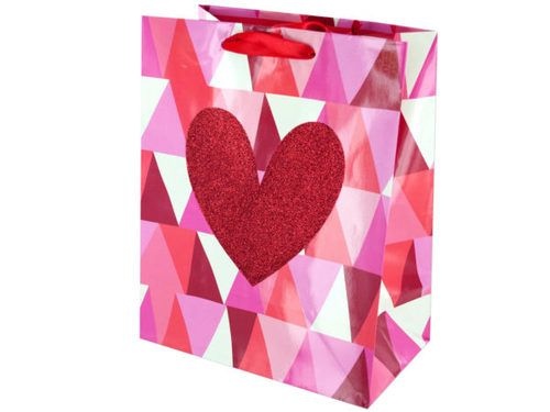 "Make someone smile with this Geometric Heart Valentine's Gift Bag featuring a glossy paper bag in a geometric design with the words with a red glitter heart in the middle and red ribbon handles. Measures approximately 7.75"" x 4.375"" x 9.75"". Comes loose."