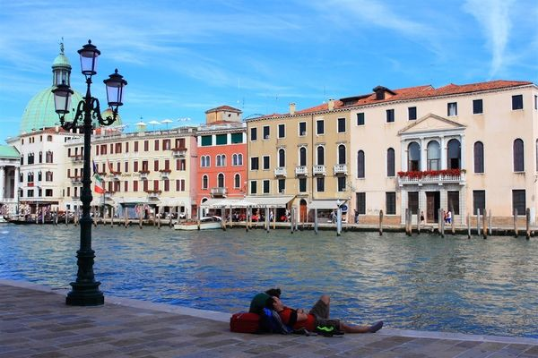 Tourist resting along the canal in Venice, Italy