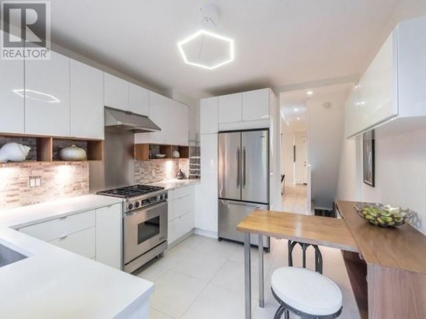 Hits of wood warm up Meghan Markle's white kitchen, while a fluorescent pendant light adds cool factor.
