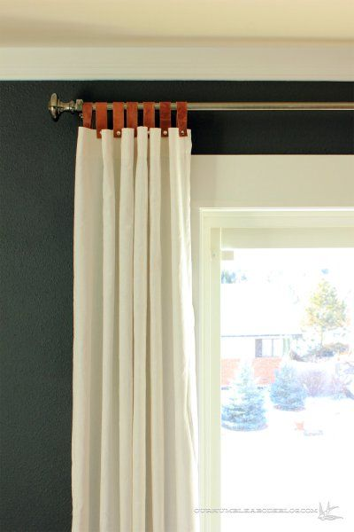 Attach leather tabs to basic curtains for an updated look.