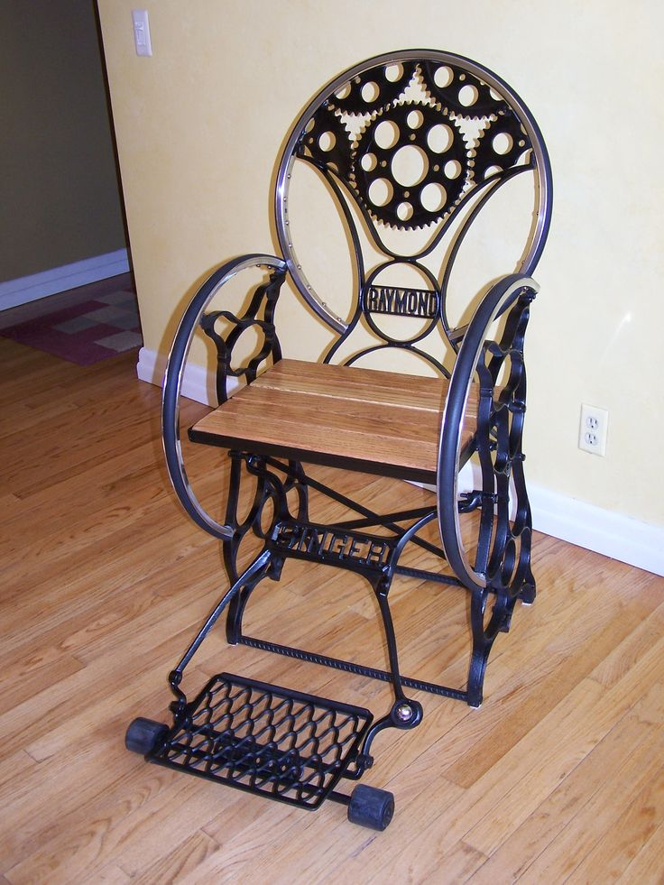 Custom Fabricated Chair….steampunk, cast iron, sewing machine bases, chrome wheels, motor cycle gears, oak stair tread boards, black rubber tubing….all salvaged items collected to create the chair. The fabrication of the chair is welded, using the ornate cast iron steel from two antique sewing machines, by Singer and Raymond. The seat was salvaged from old Ohio oak stair treads. The treadle acts as a foot rest. The finish is primed base coat with a durable satin enamel top coat The…
