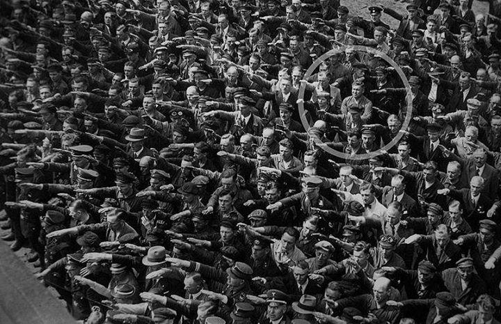 """Era August Landmesser, membro do Partido Nazista de 1931 a 1935, foi expulso ao se casar com uma judia. Depois de ter duas filhas, foi preso por """"desonrar a raça ariana"""" e só foi libertado em 1941.  Em fev. de 1944, foi enviado a unidade militar penal 999th Afrika Brigade e, logo depois, dado como desaparecido. Foi declarado morto em 1949.  Em 1991, Landmesser foi identificado por sua filha, que escreveu a história de sua família no livro A Family Torn Apart by """"Rassenschande""""."""