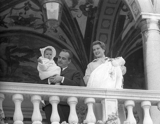 After the baptism of their second-born son Albert II Prince of Monaco, Rainier III the Sovereign Prince of Monaco appearing to his subjects holding Princess Caroline of Hanover in his arms while his wife, American actress and Princess Grace Kelly, 1958 [Getty Images]