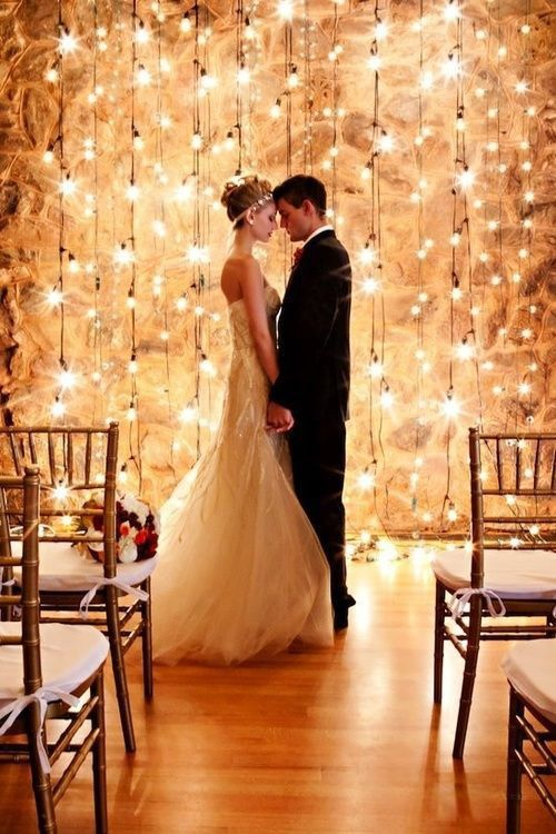 It's so simple and gorgeous. Nothing much on the chairs, and just a simple drape of lights in the back. The wall looks metallic to reflect it so well, but it might not be...