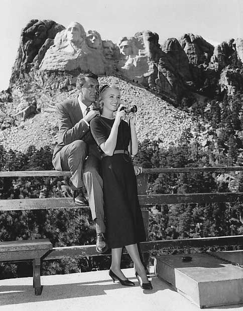 """In the shadow of the Mt. Rushmore Memorial during a location for (""""North by Northwest"""") are Cary Grant and Eva Marie Saint"""