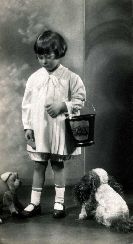 Mode. Kinderkleding. Een klein meisje in een  wit manteltje met plooien en daaronder een broek tot de knieën. Ze heeft een emmertje aan de arm en aan haar voeten staan speelgoedbeesten. Duitsland, 1926.