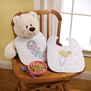 """Product # PD45586 - Stitch something special for a new little bundle of joy! Stamped cross stitch on pre-quilted and pre-finished poly-cotton bibs with hook and loop closures that are machine washable. Kit includes cotton embroidery floss, floss separators, needle, instructions. Each: 14""""L x 9""""W"""