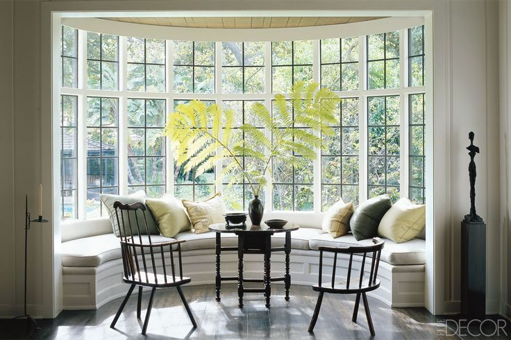 BEVERLY HILLS BAY WINDOW    A cushioned banquette with neutral-tone pillows fits the contours of a bay window at a 1920s house in Beverly Hills, California, decorated by Waldo Fernandez. A pair of Windsor chairs and a traditional English gateleg table add rustic charm.