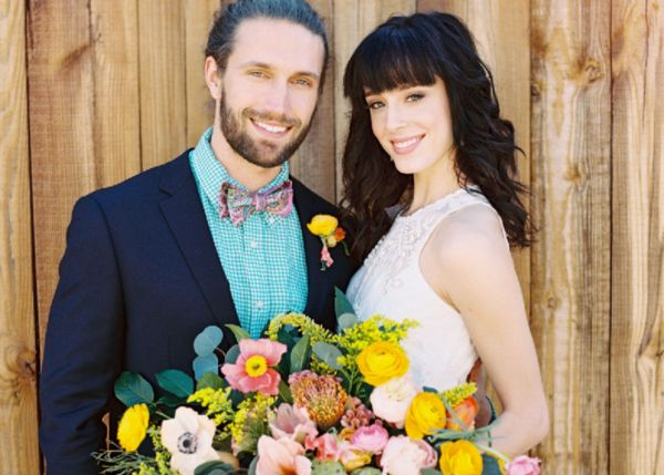 Bright yellow and pink bouquet and bride and groom at a summer wedding.