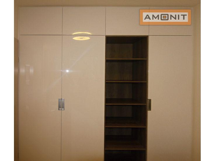 Lamino ve vysokém lesku na posuvných dveřích vestavěné skříně se zapuštěnými úchytkami