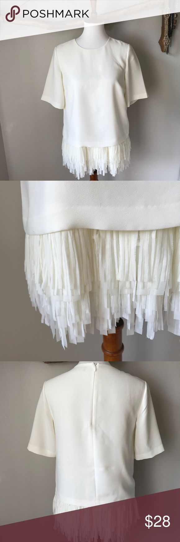 Banana Republic Fringe Blouse A fun and festive top! Relaxed fit Ivory short sleeve blouse with layers of fringe all over hem. In great used condition! Zipper in back. 100% polyester. 19 inch bust and 20 inches long before fringe. Banana Republic Tops Blouses