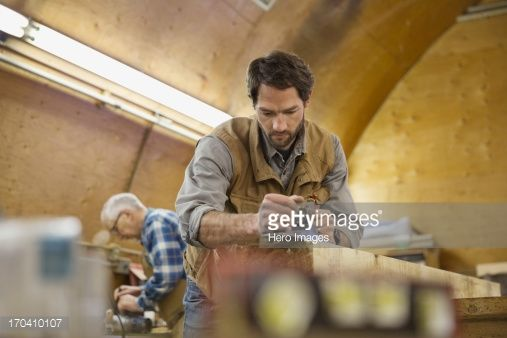 Stock Photo : Woodworker using hand plane on lumber