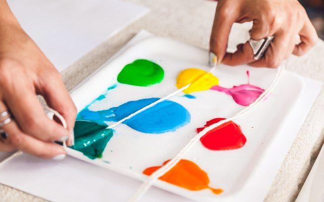 Corte dois pedaços de barbante e os encoste em diferentes porções de tinta colorida. Foto: Edu Cesar