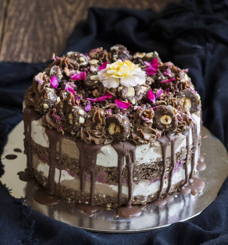 Sexy hazelnut chocolate raw vegan cheesecake with a hazelnut cookie base, swirly layers of 'notella' and vanilla cheesecake, a layer of raw brownie, raspberry chia jam and it's topped with raw 'ferrero rochers', cookie crumbs, and dried rose petals.
