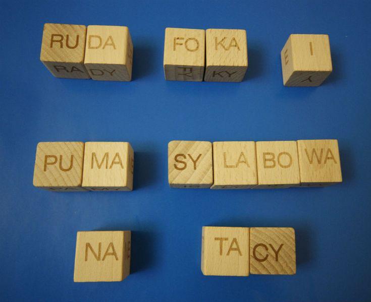 KLOCKI SYLABOWE20 drewnianych klocków, na których mieszczą się sylaby i samogłoski (razem 114).Klocki są wykonane z drewna. Wielkość jednego klocka to 2,5x2,5x2,5 cm