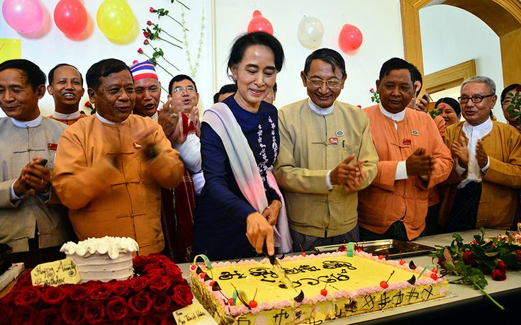 Myanmar's opposition leader Aung San Suu Kyi, centre, cuts her birthday cake as members of her National League for Democracy party sing during a celebration of her 70th birthday at a parliament building in Naypyitaw, Myanmar.