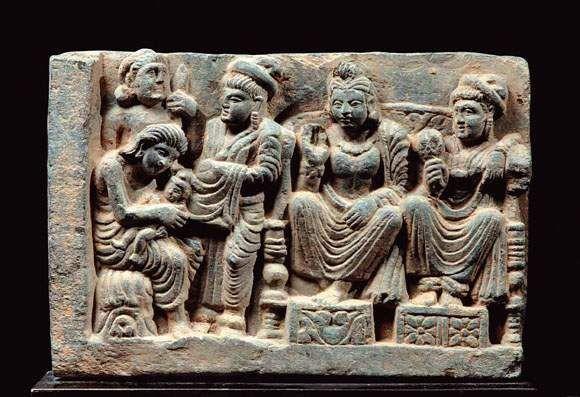 Bas-relief figurant l'interprétation de l'horoscope du prince Siddharta par un sage. A la droite du bas relief assis à l'européenne sur un trône : la reine Maya et le roi Suddhodana, parents de Siddharta. Sur la gauche du bas relief, figurent la sœur de la reine Maya et le sage sur les genoux duquel elle vient de déposer le prince Siddharta nouveau-né. Représentation rare. Schiste. Art gréco-bouddhique du Gandhara  Ier - Vè siècle H. 12 cm, L. 27,5 cm.