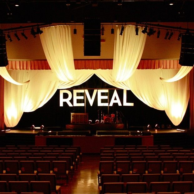"""The main """"swoop"""" was made up of six 10′ wide x 20′ long panels. The clouds (fabric hanging in front of the proscenium) were shear fabric that they had from another set. The word """"Reveal"""" was cut out of foam board. They used a projector to trace the word Reveal in the same font as in the series graphic and then cut it out, paint it white, hung it from a frame on a rolling platform."""