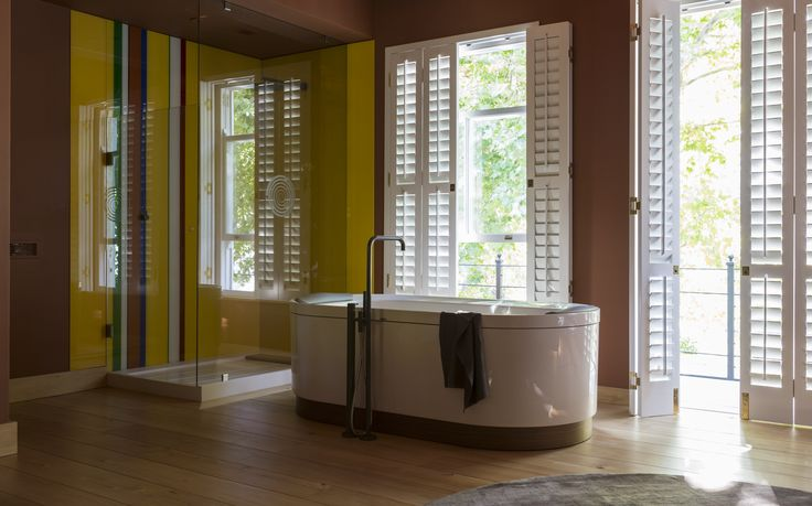 The Hoesch bath with the grey finished Vola bath column is beautifully framed with the white shutters.