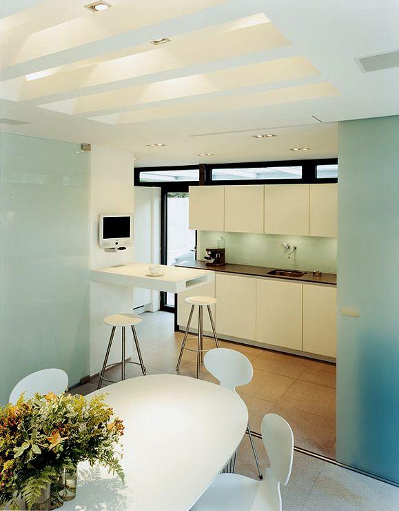 Küche mit geschlitzter Lichtdecke, dunkle Arbeitsplatte und Glasrückwand