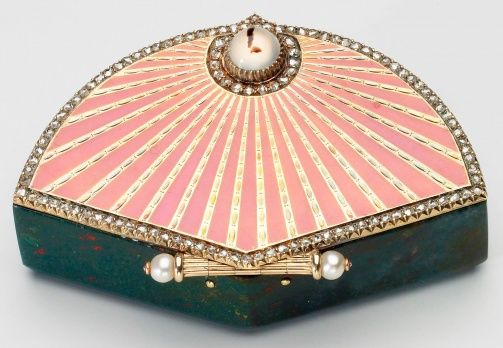 This Fabergé fan-shaped box formed part of Queen Mary's collection. The body of the box is of bloodstone while the lid, in the shape of a fan, is of alternate tooled gold and pink guilloché enamelled stripes, edged with brilliant diamonds. The handle of the fan forms the hinge and is set with pearls, while the pushpiece is a cabochon moonstone. Workmaster Michael Perchin, 1903.