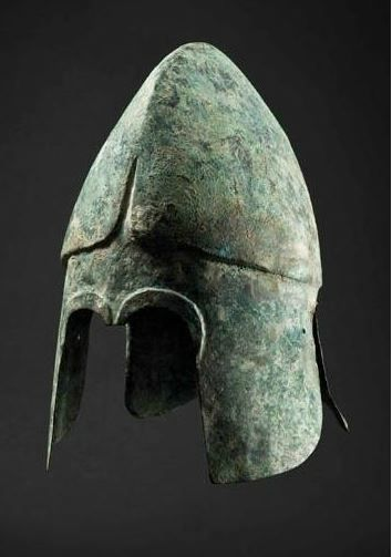 Late Chalcidian helmet with regional characteristics (type II) of the so-called Thracian group. High skull with pronounced, slightly rounded crest ridge. The former distinctly set off against the forehead below, the cheek pieces and the neck guard.  The edges of the eye openings framed by broad borders in repoussé, with a short nasal bar set in between, ending in a straight horizontal rim, 31 cm high. Private collection, from Hermann Historica auction