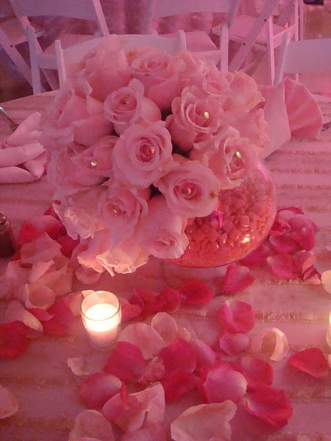 * Pink roses, petals and candles make a beautiful centerpiece for the table.