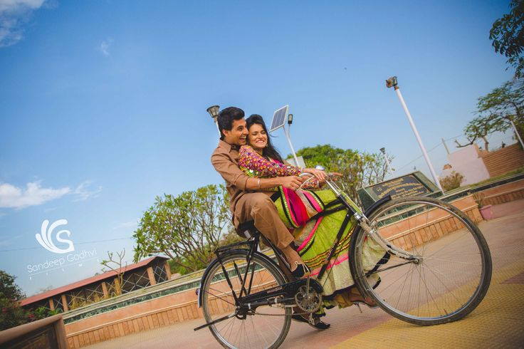 Couple shoot on a bicycle in a village near Rajasthan. An open blue sky with colorful bride to be with his groom makes a quirky picture for the shoot.