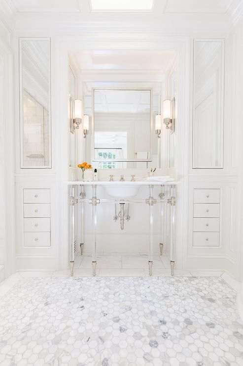 Chic bathroom features a 6 leg nickel and glass washstand topped with marble placed under a satin nickel mirror flanked by floor to ceiling built in cabinets accented with mirrored cabinet doors alongside a marble hexagon tile floor.