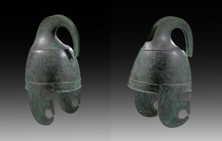 Urartian or Neo-Assyrian helmet with protruding crest, 9th - 8th century B.C. Manufactured from two riveted, separately worked halfs with a high protruding crest-holder. The cheek-pieces worked separately and riveted with drop-shaped openings for eyes and mouth. Along the rim tiny rivet holes for the inlay and the crest, 37,5 cm  high. Private collection, from Gorny & Mosch auction