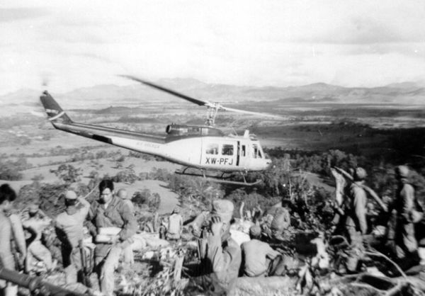 """ourforgottenwars: """"Air America (CIA) Bell 205 helicopter leaving a Hmong Fire Support Base atop a hill in the south-eastern portion of the Laotian """"Plain of Jars"""" in 1969. """""""