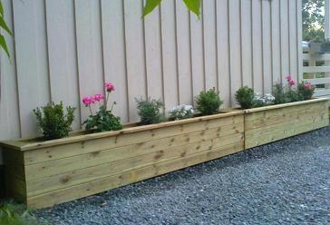 Store isolerte blomsterkasser fra Blomsterkasseriet. Blomsterkassene står på gårdsplass/ singelbelagt.