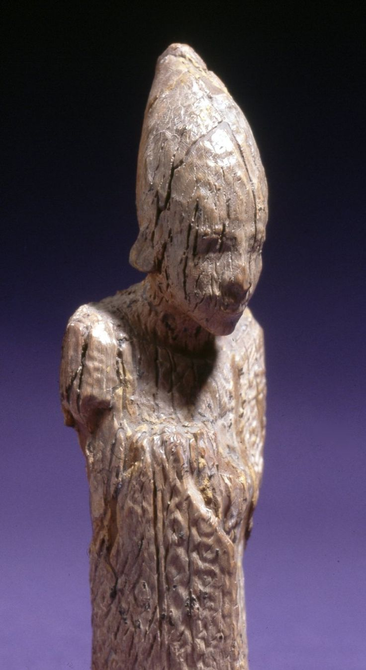 Statuette of a king: the figure of a beardless king wearing a white crown, the weight of which seems to be pushing out the tops of his huge ears. Wrapped in a short, stiff robe, he strides forward on...