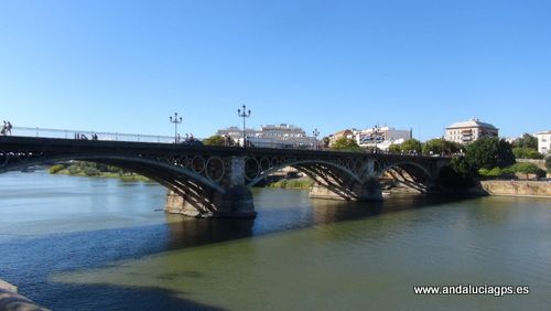 #Sevilla capital - Puente de Isabel II GPS 37.386222, -6.002333 Conocido popularmente como Puente de Triana, que une el centro de la ciudad con el barrio de Triana cruzando el río Guadalquivir y que vino a sustituir en el siglo XIX a un viejo puente de barcas que existía en su lugar, constituyendo el puente de hierro más antiguo conservado en España. Su construcción finalizó en 1852, bajo el reinado de Isabel II, motivo por el que ostenta dicho nombre.