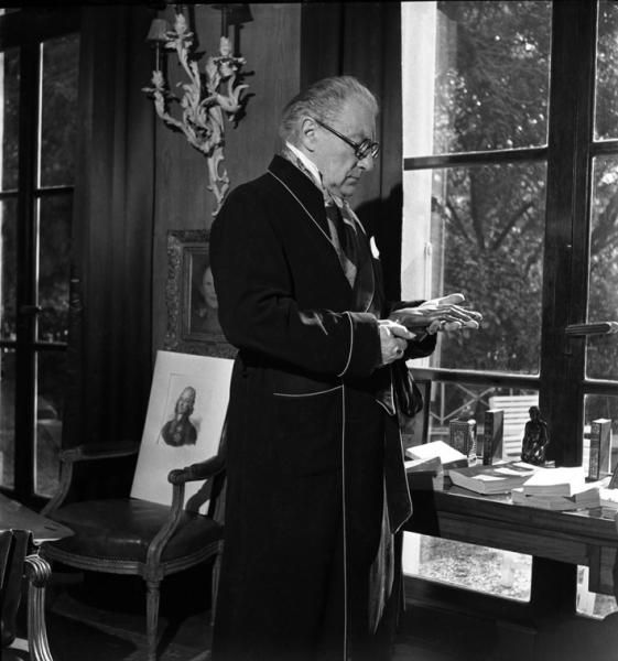 Émile Savitry - Sacha Guitry at home looking at a sculpture of a hand, Paris about 1940