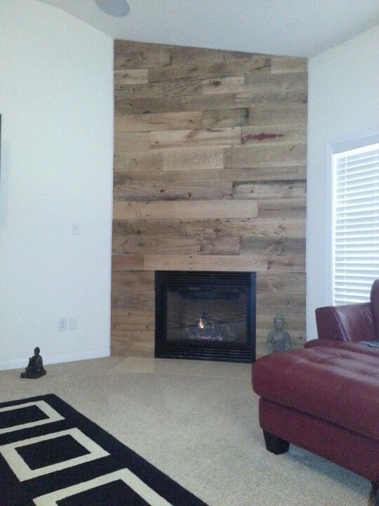 Another corner fireplace using reclaimed wood.