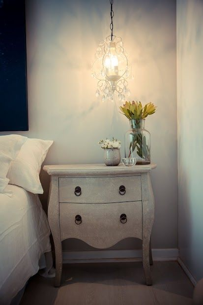 Bedside table with low hanging chandelier