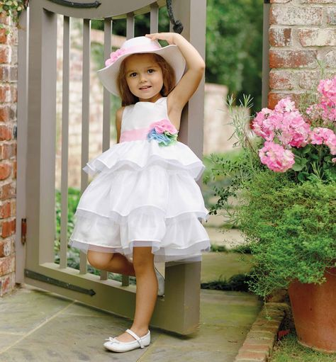 Dress up baby in pastels for the Spring season in our beautiful, ivory silk dress. This fancy baby dress with tiered skirt features a pink sash and multi-colored chiffon flowers at the waist. Makes a perfect Sunday dress for baby girl and is a wonderful choice for special occasions such as Easter. Pictured with Flower Straw Hat and Light Pink Chiffon Flower Soft Headband (each sold separately). Available in sizes 0-6 months, 6-9 months, 9-12 months, 12-18 months, 2T, 3T, 4T and 5T.
