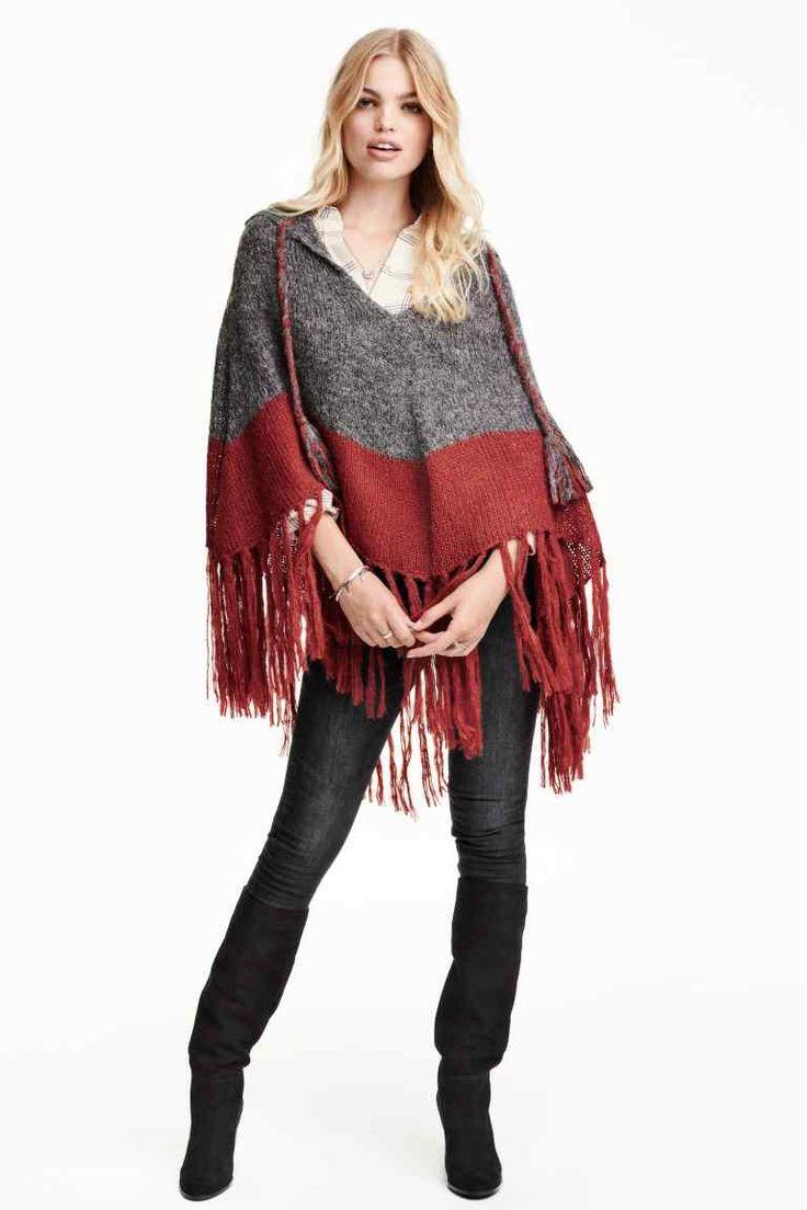 Poncho con flecos: Poncho de punto con capucha en tejido suave con lana de alpaca en la trama. Modelo con escote de pico y tira de atar con borlas de adorno en los extremos. Acabado de flecos.