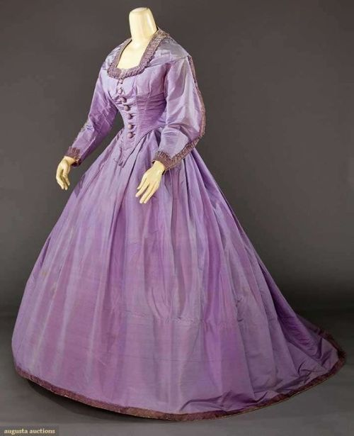 LILAC SILK TAFFETA AFTERNOON GOWN, 1865  Bodice w/ square neckline  Velvet trim to sleeves, cuffs & neckline, 7 velvet dome buttons, full skirt w/ back cartridge pleating, velvet hem trim