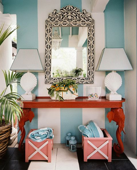The Elephant In The Room: Ruthie Sommers' alfresco pavillion feels like a Palm Beach retreat.  The bright red elephant console contrasts beautifully against the white-and-blue striped wall and beach towels, stowed below.